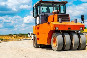Pneumatic tire roller compacting soil
