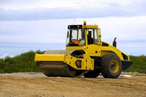 Smooth drum roller compacting soil