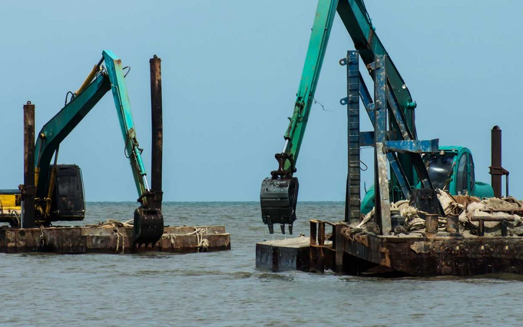 Two excavators in the water dredging contaminated soil